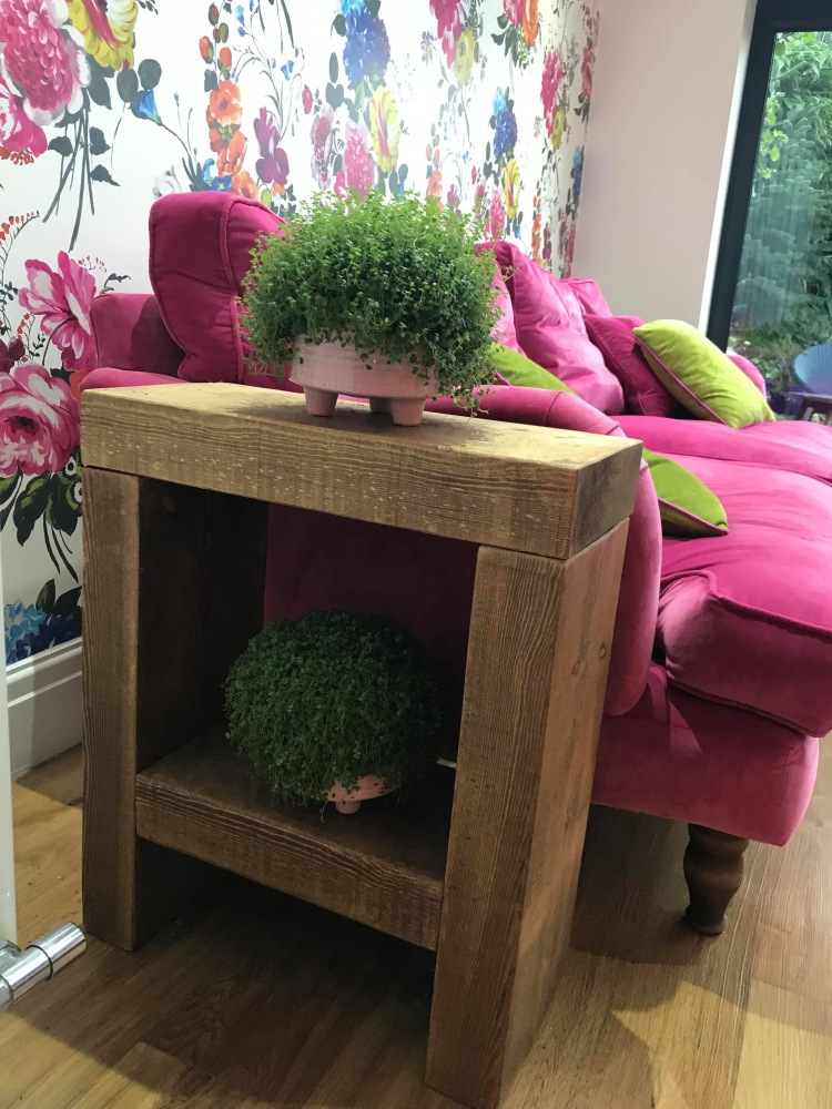 small rustic solid wood side table with houseplants in pink living room