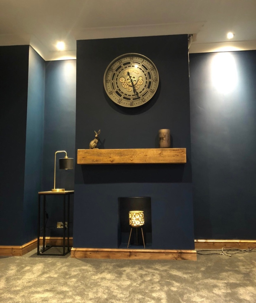 Solid oak mantel on dark blue walls with matching skirting boards
