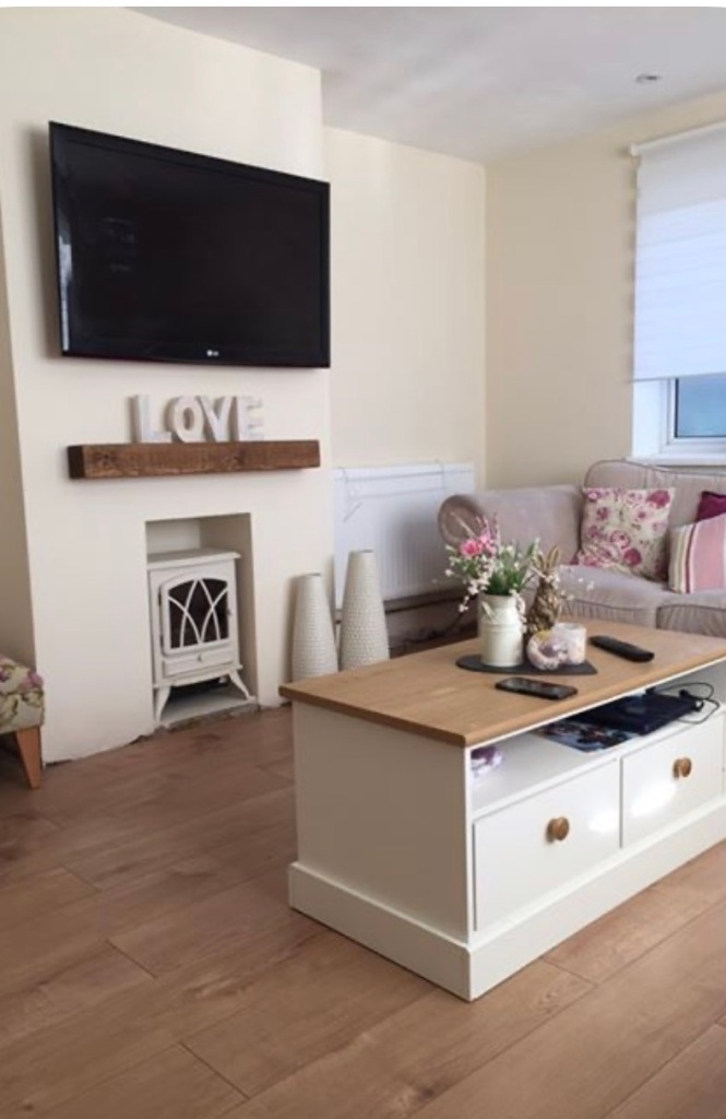 cream fireplace wall with woodburner, large tv and solid wood chunky mantel shelf