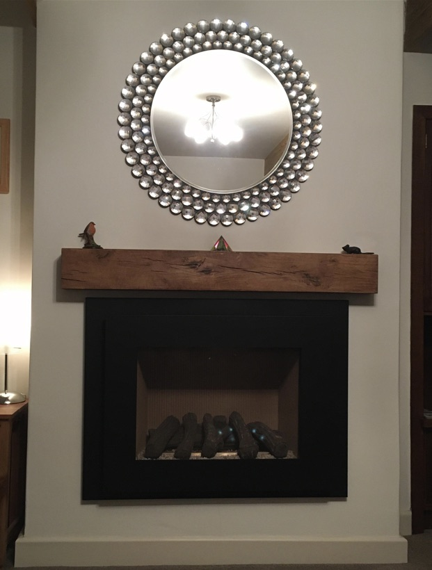 chunky oak beam above electric fire