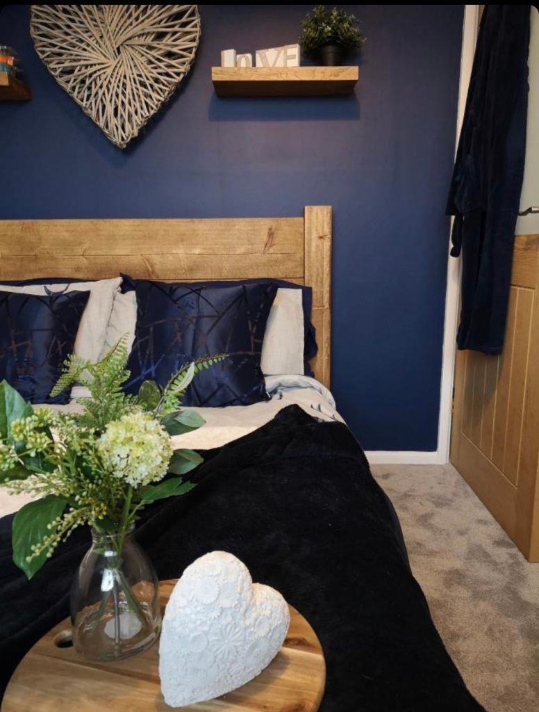 chunky solid wood bed in dark blue bedroom