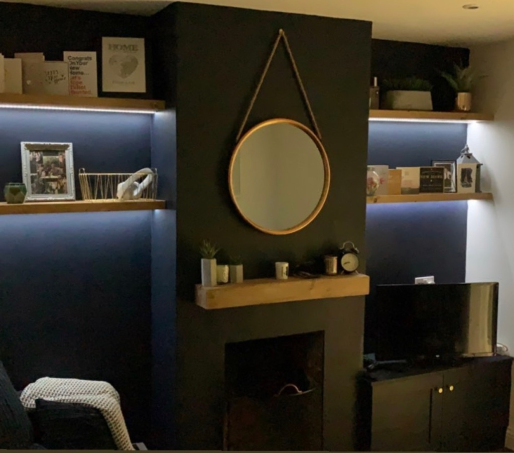 sets of alcove floating shelves with oak beam mantel on dark blue walls with back lighting