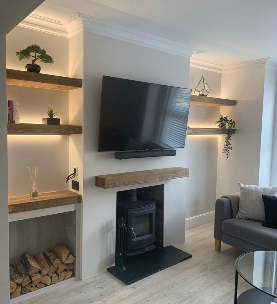 set of back lit alcove floating shelves and oak mantel shelf on white walls with woodstore