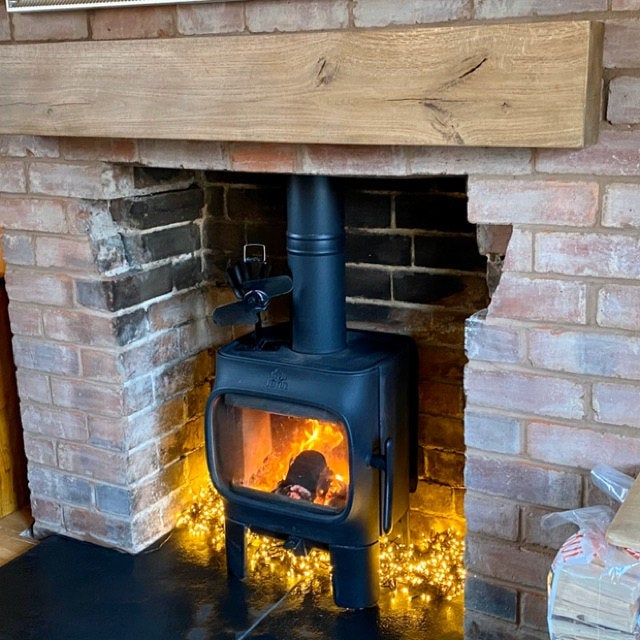 exposed brickwork fireplace with wood burner and large chunky solid oak mantel beam