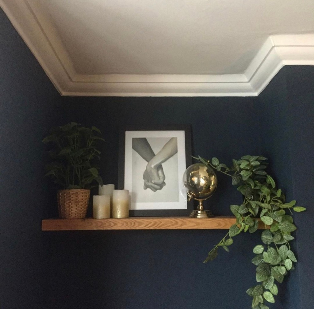 dark blue walls living room with solid wood floating shelves in alcove