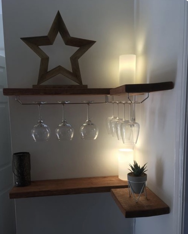 white walls with corner of solid wood rustic floating shelves, under shelf wine glass holders and candles