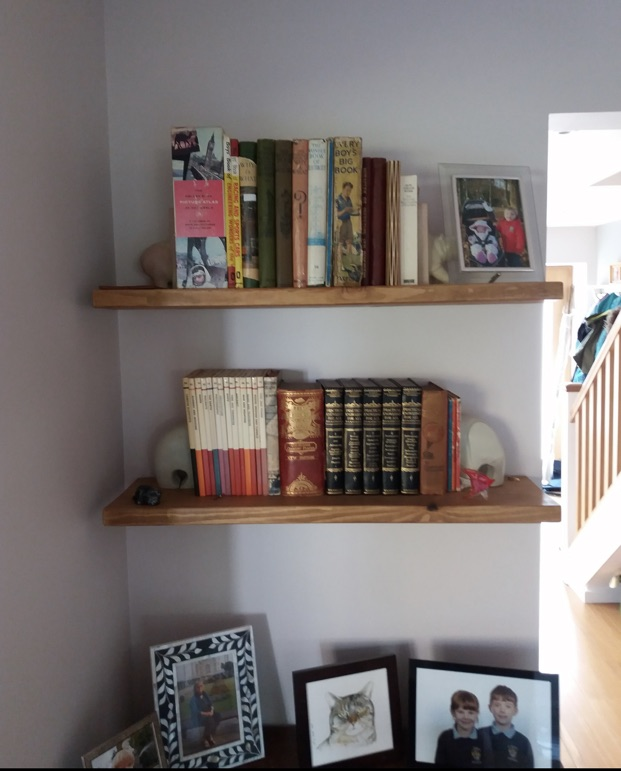 rustic wooden floating shelves on white wall holding books