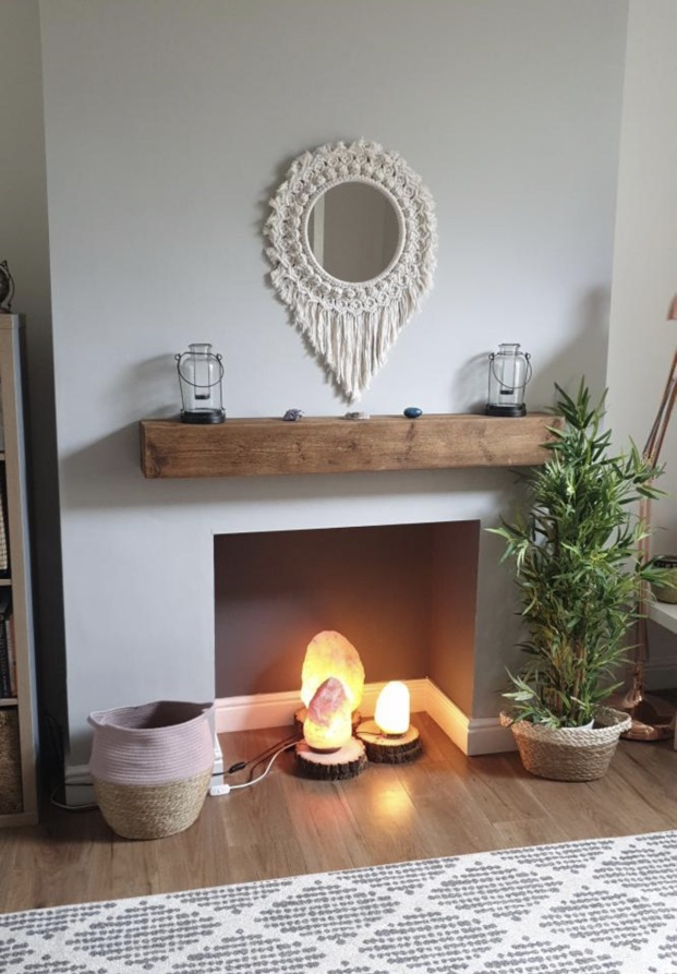 chunky oak beam mantel above open hearth with himalayan salt lamps and macrame mirror