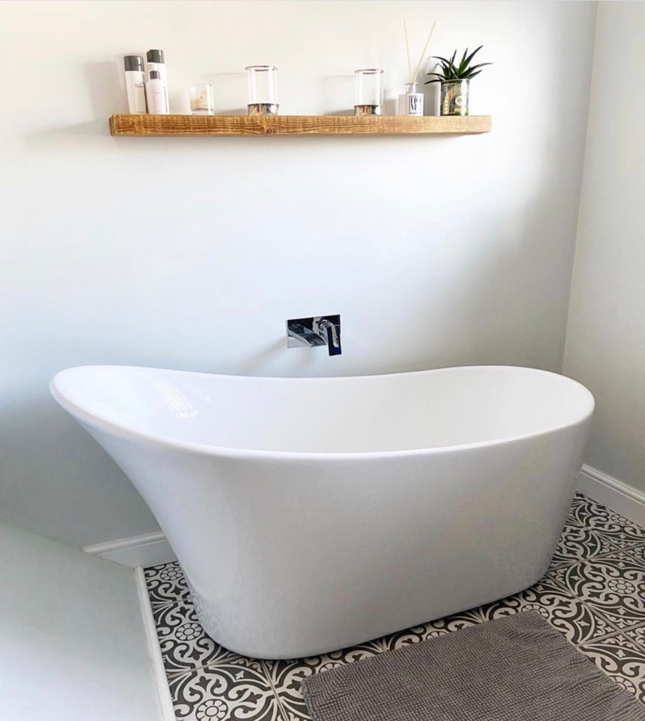 rustic floating shelf in white bathroom with freestanding bath