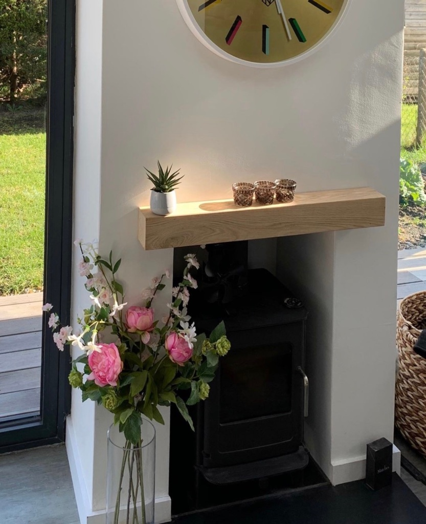 white fireplace with solid oak mantel, chunky oak mantel with flowers and garden views