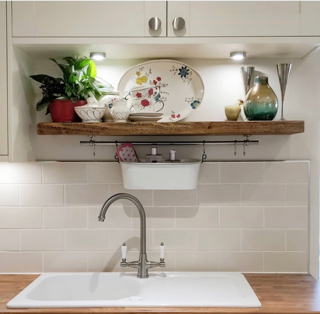 Rustic wooden floating shelf above sink in white country kitchen