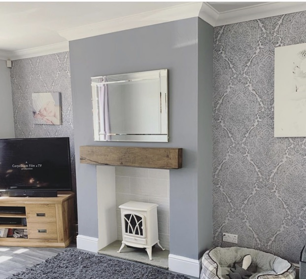 chunky oak mantel over white burner on lilac painted and wallpaper walls