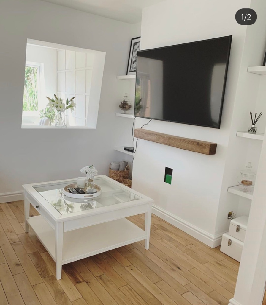 white room with large tv and floating mantel shelf