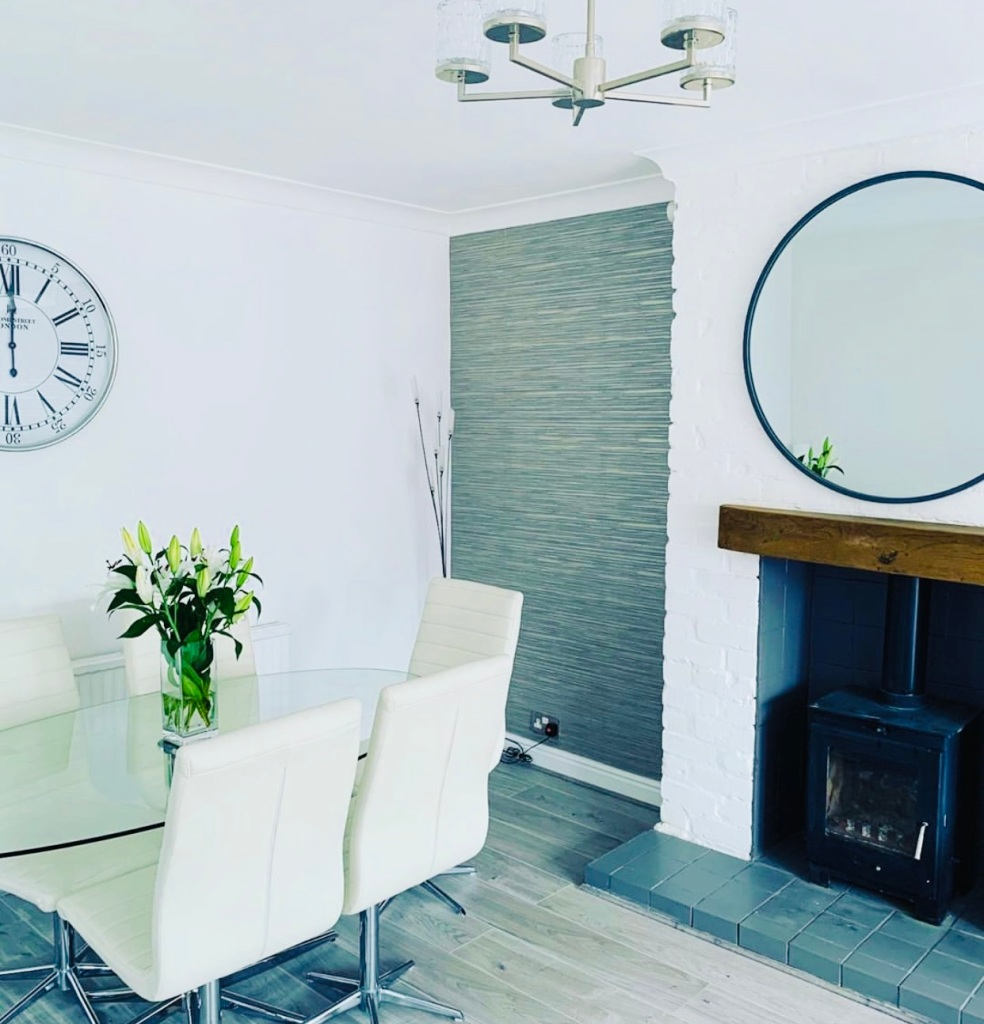 whitewashed brickfireplace with large circular mirror, oak mantel, wood burner and tiled hearth.
