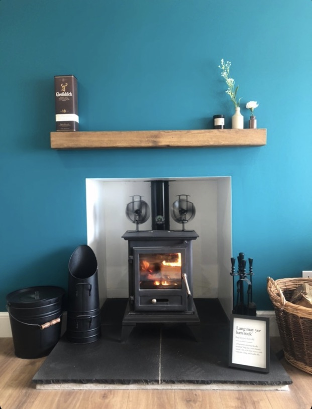 chunky oak mantel over black wood burner and on a teal blue wall