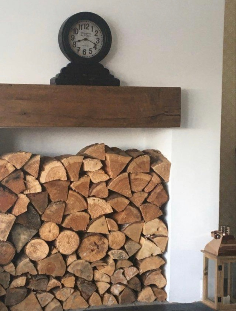 chunky oak mantel beam over wood store on white wall