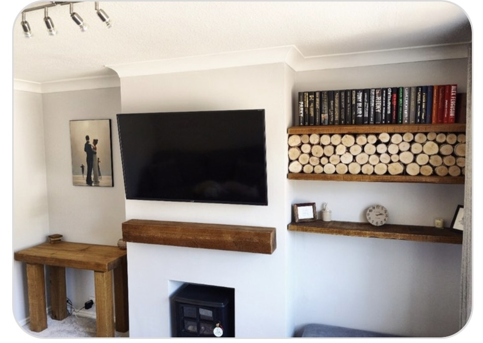 Chunky solid wood coffee table, floating oak mantel and floating alcove shelves on white walls.
