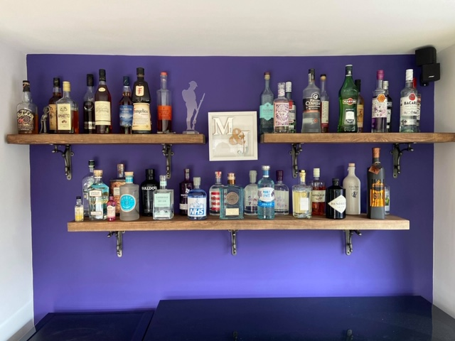 Metal Brackets and Solid Wood Shelving holding up a drinks collection on a purple wall.