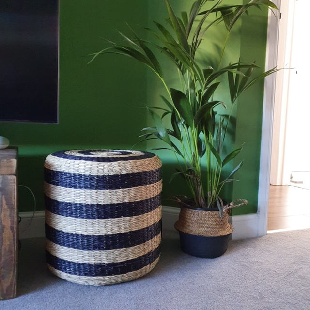 black and white seagrass pouffe in a sitting room