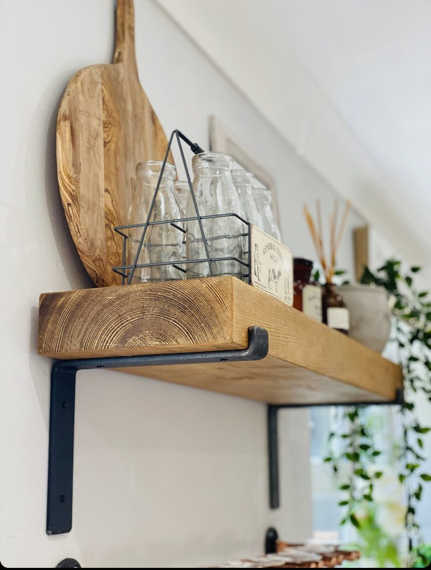 Solid wood shelf with metal brackets, in kitchen by window