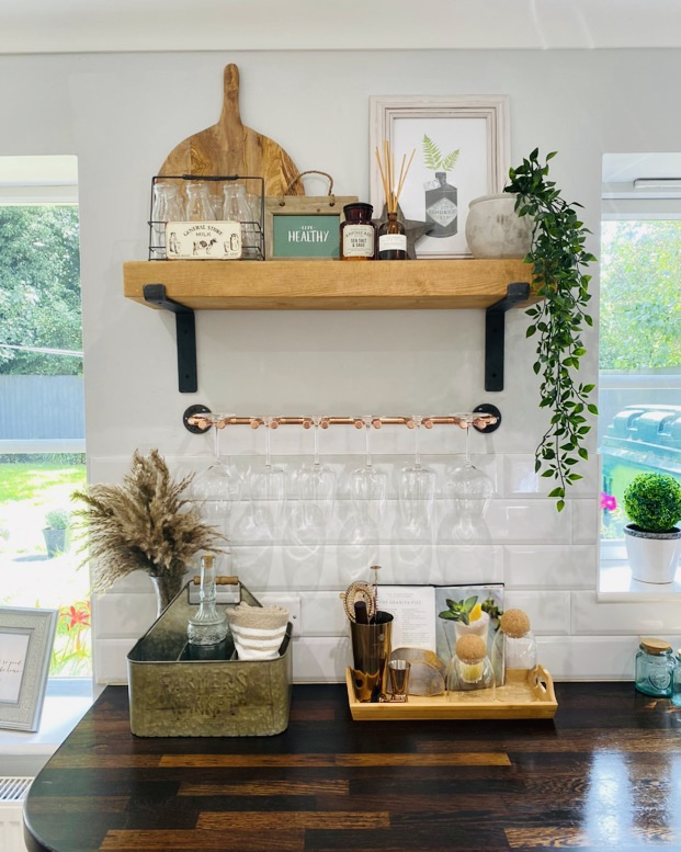 bracket shelf with rustic wooden shelf above kitchen work surface in a home.