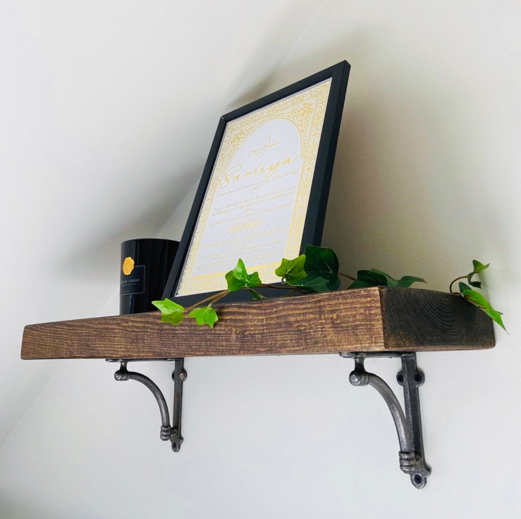 solid wood shelf with metal brackets and house plants on top.