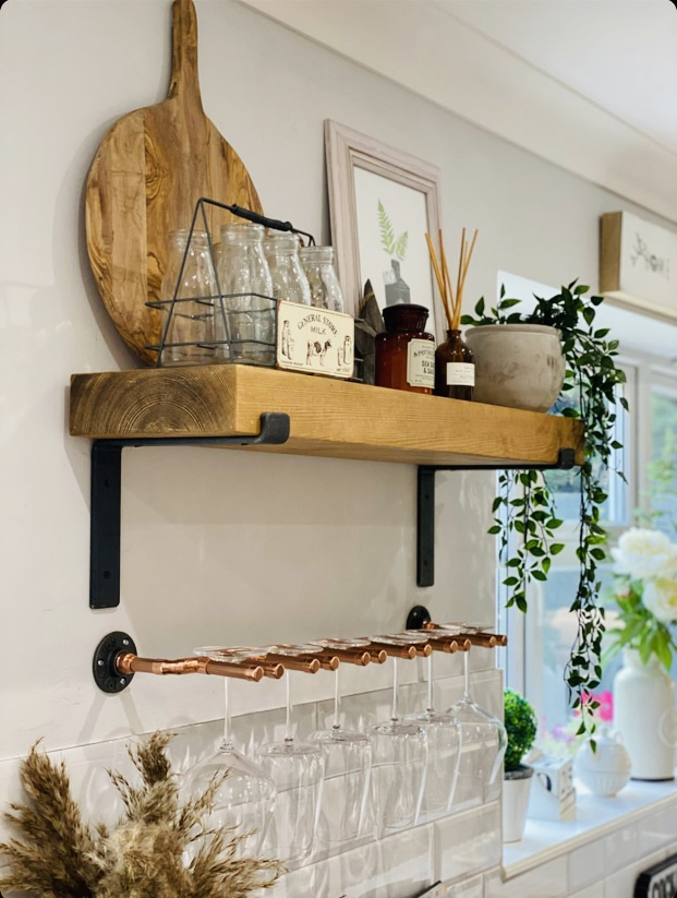 Solid wood shelf with metal brackets, in kitchen with copper wine glass holder underneath