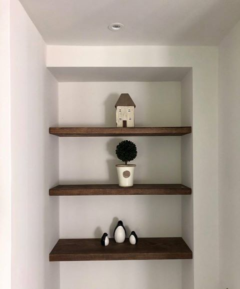 three solid wood shelves in an alcove.