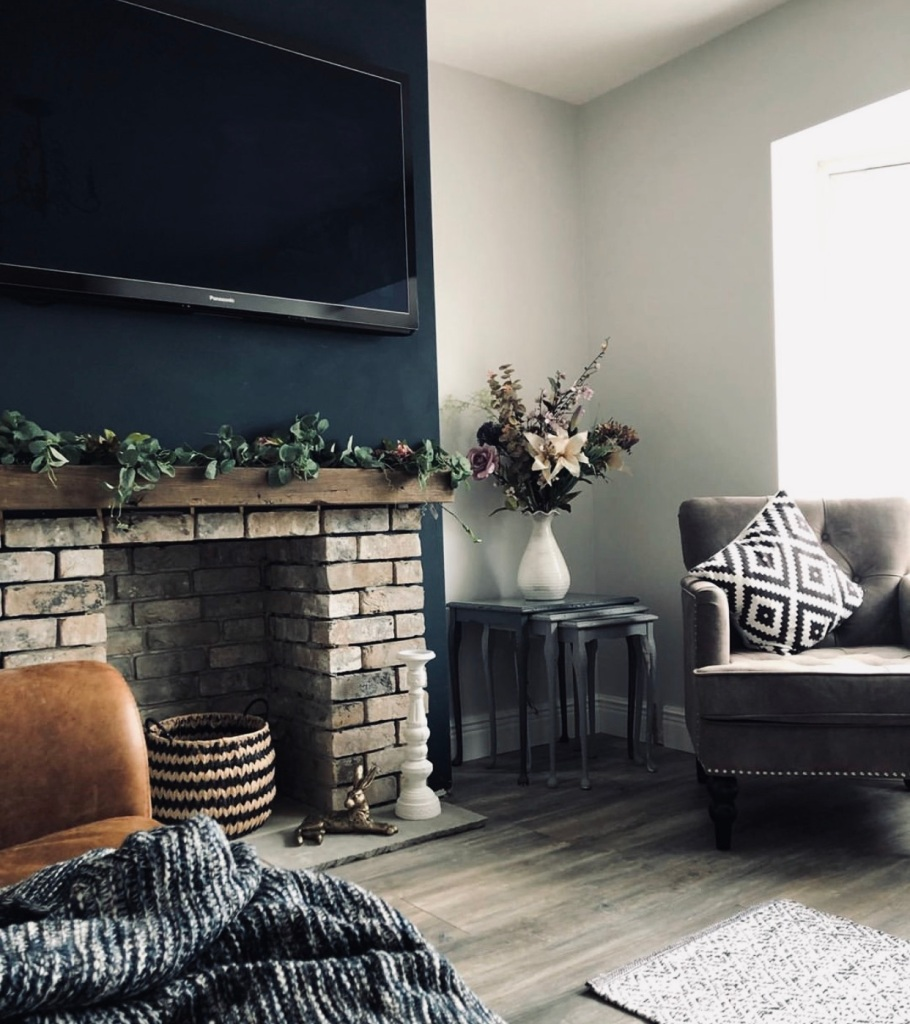 oak mantel on exposed brick fireplace on dark wall in living room