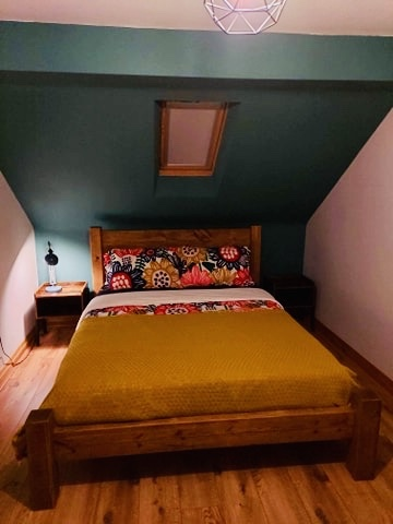Solid Wood Bed Frame in Attic bedroom with green and mustard yellow colour scheme.