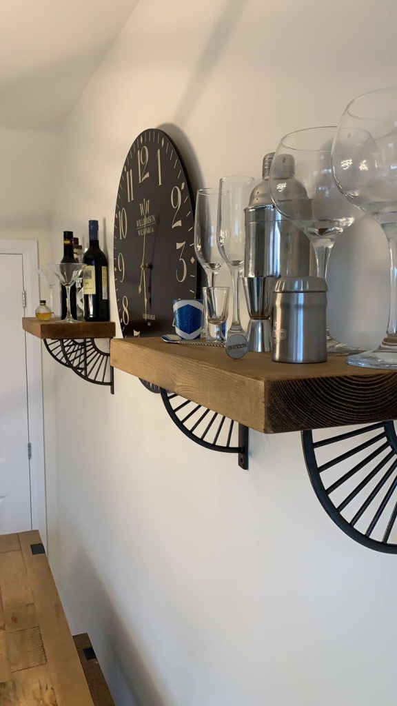 bracket shelves with metal brackets and solid wood shelves holding cocktails and alcoholic drinks