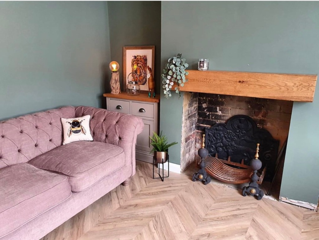chunky oak mantel beam on green fireplace wall with pastel pink velvet sofa.