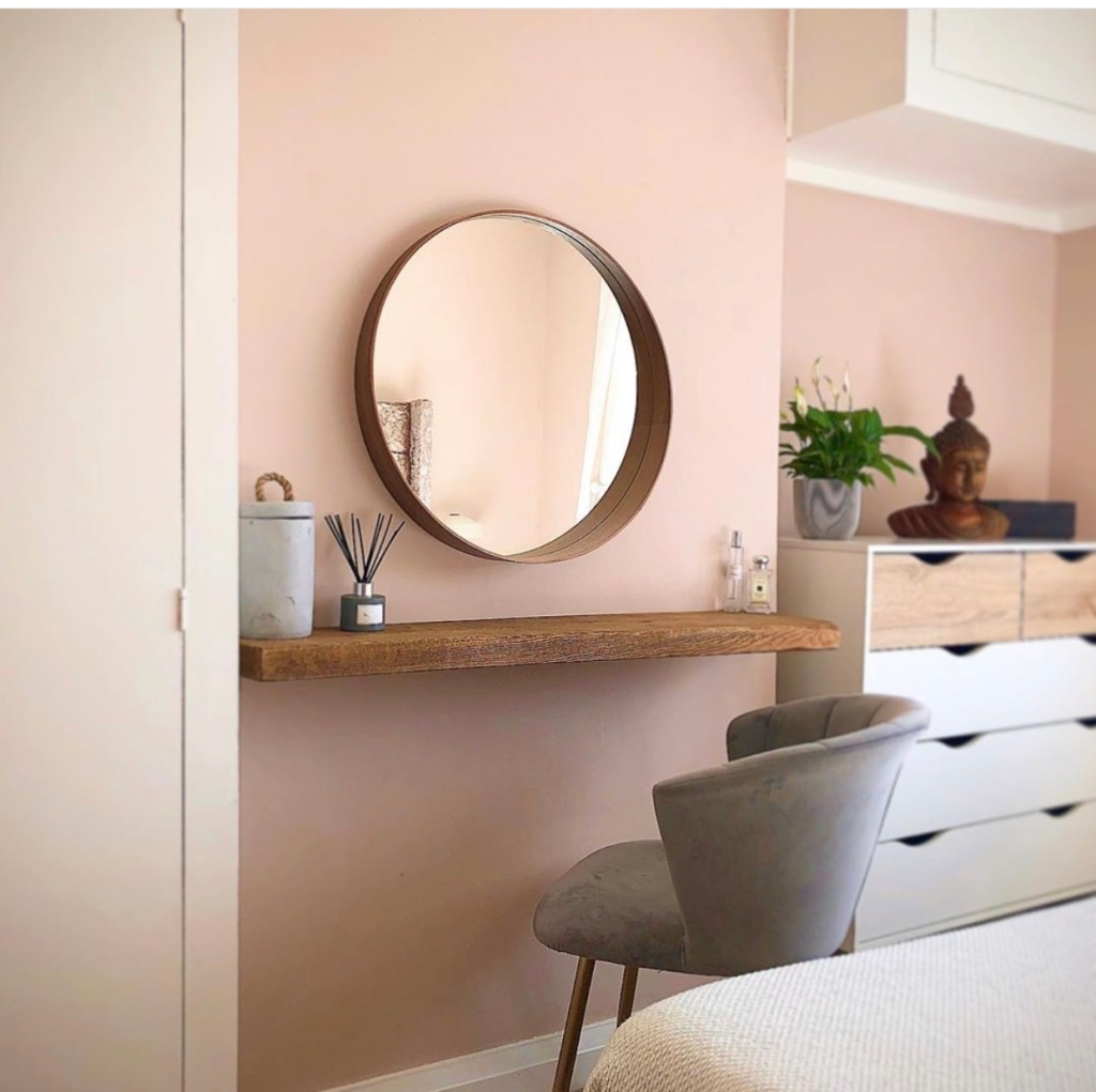 Pastel pink bedroom with floating shelf as dressing area