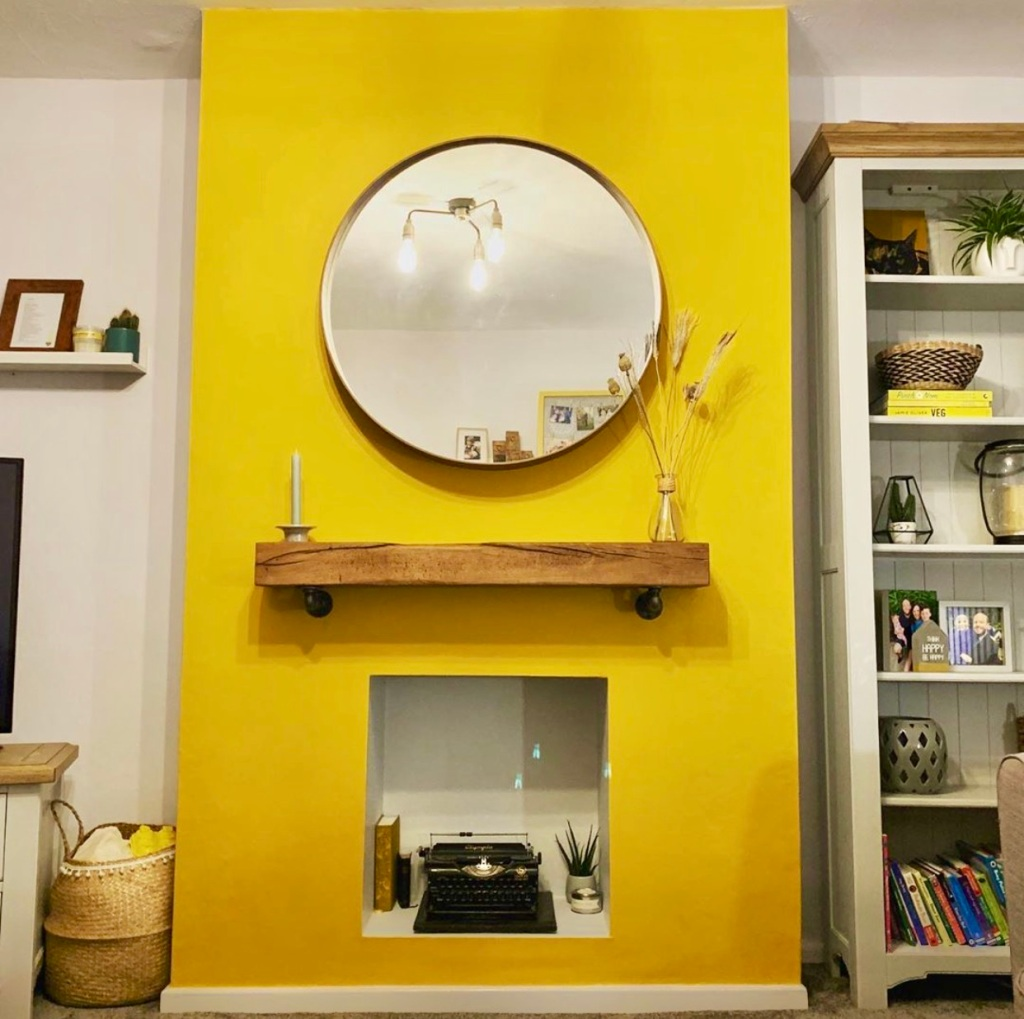 yellow fireplace with industrial style bracket shelf as mantel