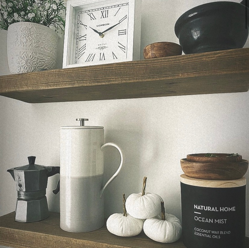 monochrome styling on solid wood floating shelves in kitchen