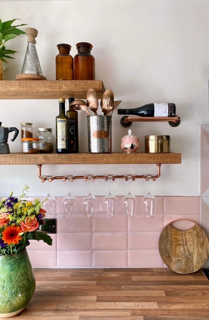 rustic floating wooden shelves with copper wine glass holder, in kitchen with pink tiles.