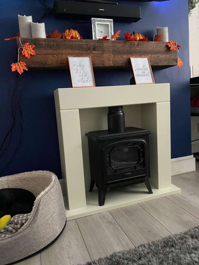 solid walnut waxed mantel beam on navy blue wall with woodburner. decorated for autumn