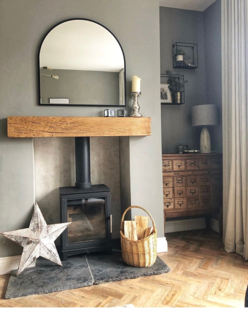 solid oak mantel in english oak against grey wall with wood burner and slate hearth.