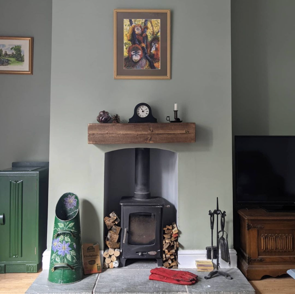 Rustic chunky mantel beam on green wall above wood burner and wood store